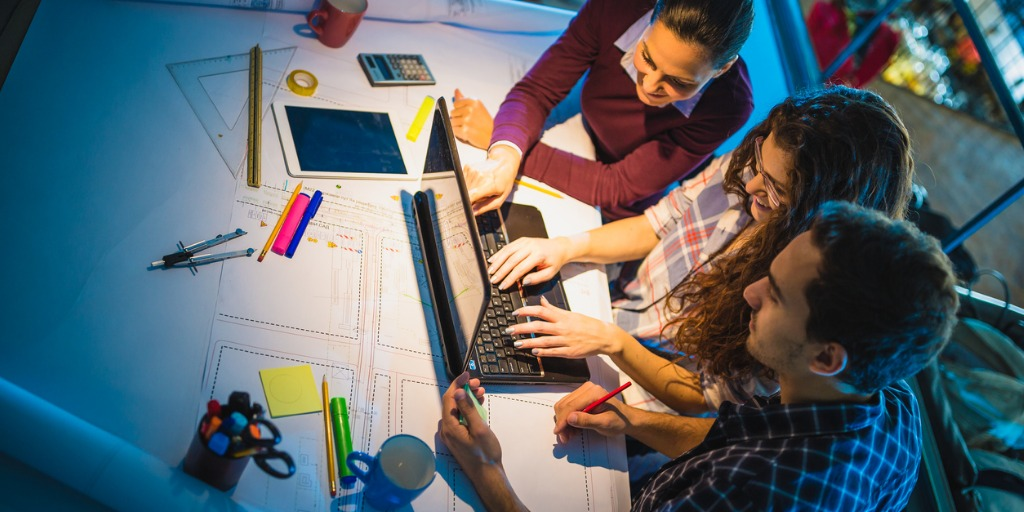 working-late-group-of-young-architects-working-late-in-office-picture-id873882140